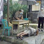 Seorang wisatawan yang tidak memakai masker dihukum push up oleh tim yustisi saat operasi di kawasan wisata Kintamani. Foto: Lintasnusanews.com/Ist